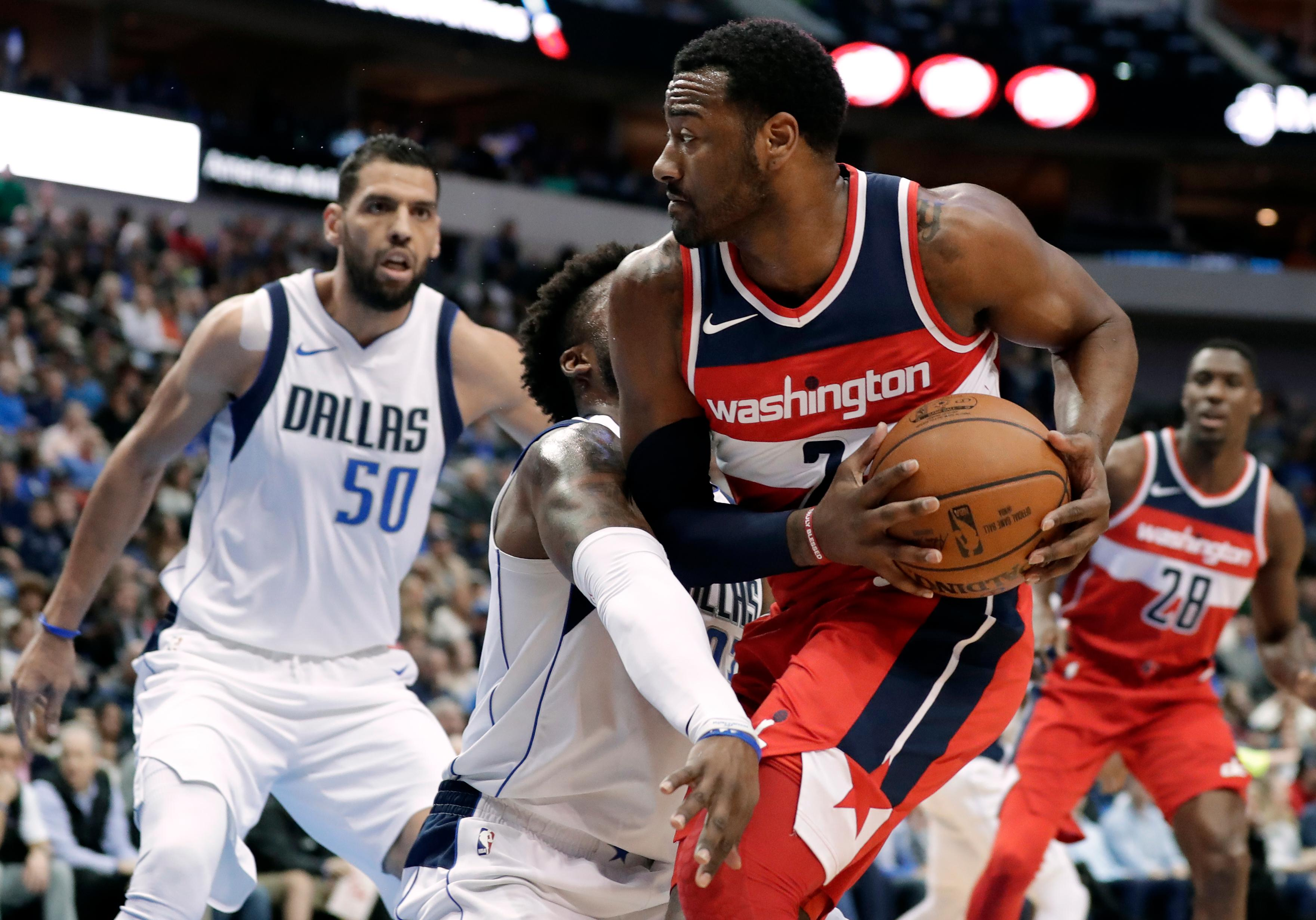 Dallas Mavericks guard Wesley Matthews, center left, and Salah Mejri (50), of Tunisia, defend as Washington Wizards' John Wall (2) works for a shot opportunity in the first half of an NBA basketball game, Monday, Jan. 22, 2018, in Dallas. (AP Photo/Tony Gutierrez)