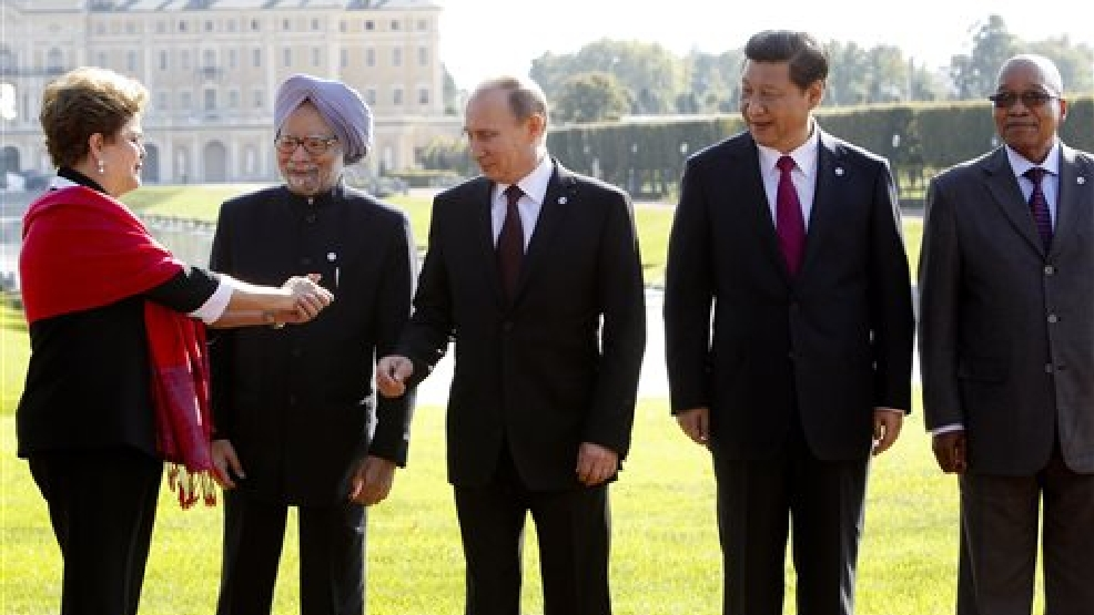 In this Sept. 5, 2013 file photo, from left, Brazil's President Dilma Rousseff gestures to then Indian Prime Minister Manmohan Singh, Russia's President Vladimir Putin, China's President Xi Jinping and South African President Jacob Zuma, as they gather for a group photo after a BRICS leaders' meeting at the G-20 Summit in St. Petersburg, Russia. In another sign of the shifting balance of power in the world economy, emerging market powers Brazil, Russia, India, China and South Africa are launching a $100 billion development bank to challenge the U.S.-dominated World Bank and help finance $4.5 trillion worth of infrastructure projects. (AP Photo/Sergei Karpukhin, Pool, File)