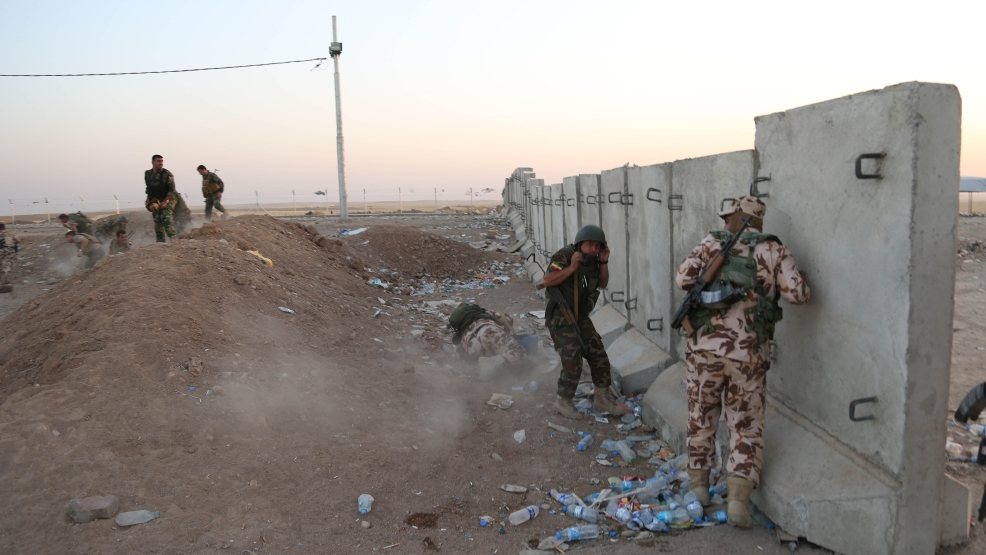 Kurdish Peshmerga fighters take cover during airstrikes targeting Islamic State militants near the Khazer checkpoint outside of the city of Irbil in northern Iraq, Friday, Aug. 8, 2014. The Iraqi Air Force has been carrying out strikes against the militants, and for the first time on Friday, U.S. war planes also directly targeted the group, which controls large areas of Syria and Iraq. (AP Photo/Khalid Mohammed)
