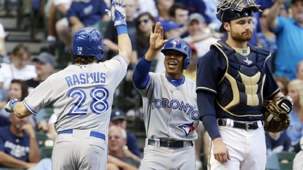 Milwaukee Brewers catcher Jonathan Lucroy reacts as Toronto Blue Jays' Colby Rasmus (28) is congratulated by teammate Edwin Encarnacion after Rasmus  hit a two-run home run during the ninth inning of a baseball game Wednesday, Aug. 20, 2014, in Milwaukee. (AP Photo/Morry Gash)
