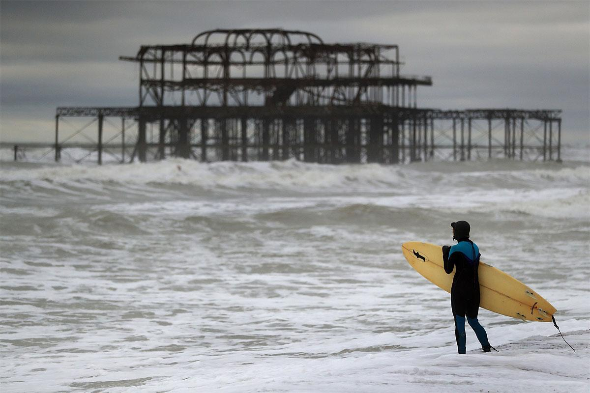 A surfer prepares to enter the sea near the old West Pier in Brighton, south east England, as a storm, Storm Angus, the year's first big winter storm in Britain, lashes England's south coast, Sunday Nov. 20, 2016. Forecasters say winds of 68 mph (110 kph) hit the south coast early Sunday, with a gust of 97 mph (156 kph) recorded offshore. (Andrew Matthews/PA via AP)
