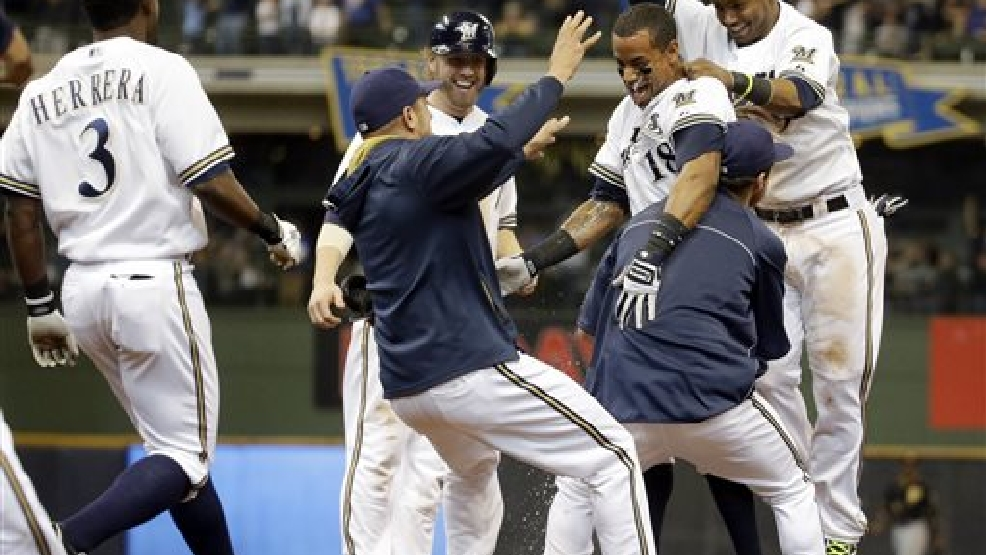 Milwaukee Brewers' Khris Davis is mobbed by teammates after hitting a walk-off two-run single during the ninth inning of a baseball game against the Pittsburgh Pirates Thursday, May 15, 2014, in Milwaukee. The Brewers won 4-3. (AP Photo/Morry Gash)