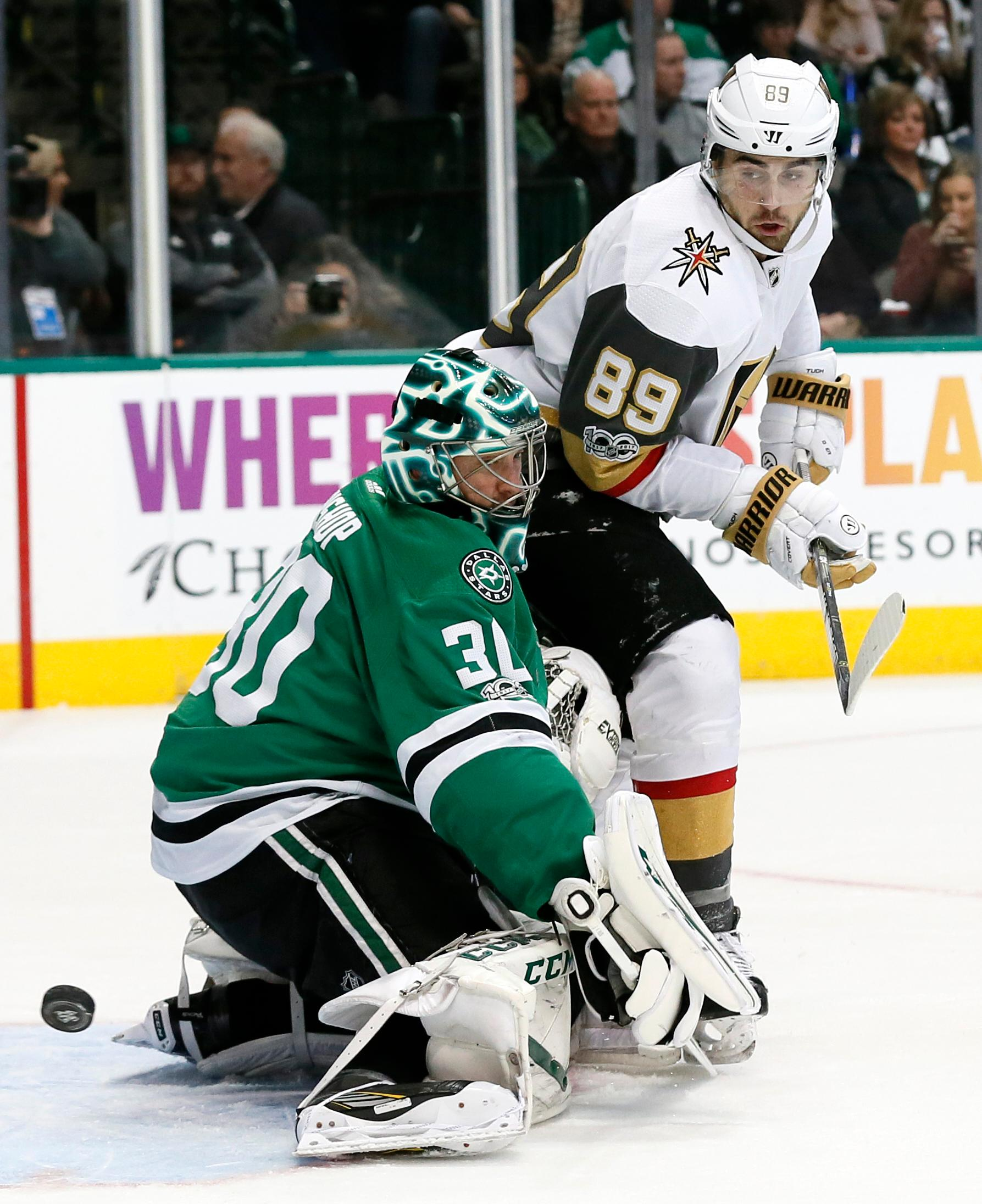 Dallas Stars goalie Ben Bishop (30) deflects a shot as Vegas Golden Knights right wing Alex Tuch (89) watches during the second period of an NHL hockey game, Saturday, Dec. 9, 2017, in Dallas. (AP Photo/Tony Gutierrez)