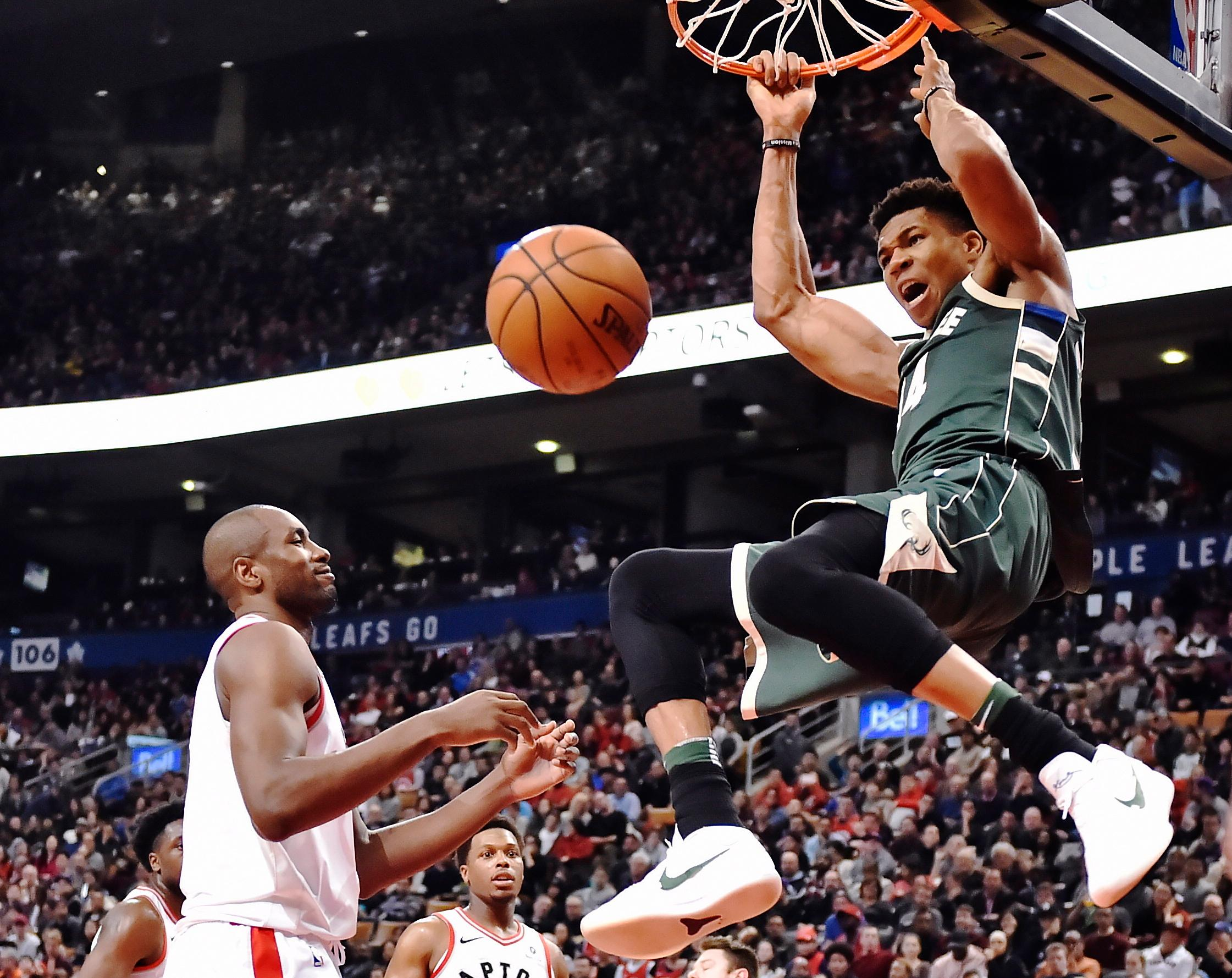 Milwaukee Bucks forward Giannis Antetokounmpo (34) dunks as Toronto Raptors forward Serge Ibaka (9) looks on during the second half of a game in Toronto on Monday, Jan. 1, 2018. (Frank Gunn/The Canadian Press via AP)