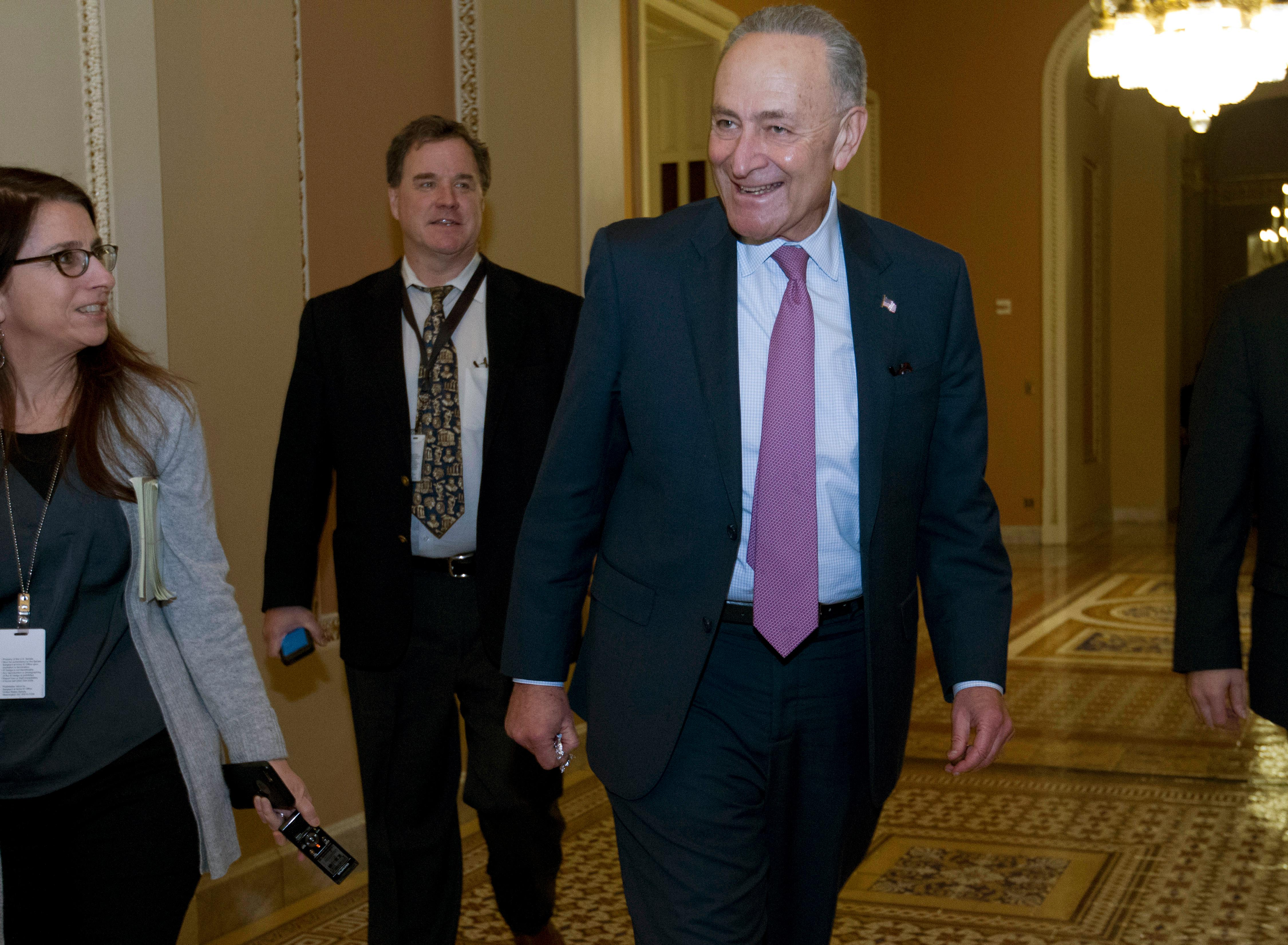 Senate Minority Leader Chuck Schumer, D-N.Y., walks to his office as he answers reporters, at the Capitol, Thursday, Feb. 8, 2018, in Washington. (AP Photo/Jose Luis Magana)