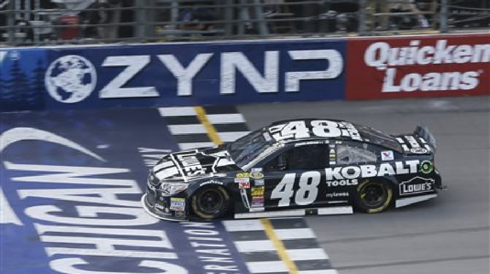Jimmie Johnson takes the checkered flag at the NASCAR Quicken Loans 400 auto race at Michigan International Speedway, Sunday, June 15, 2014, in Brooklyn, Mich. (AP Photo/Carlos Osorio)