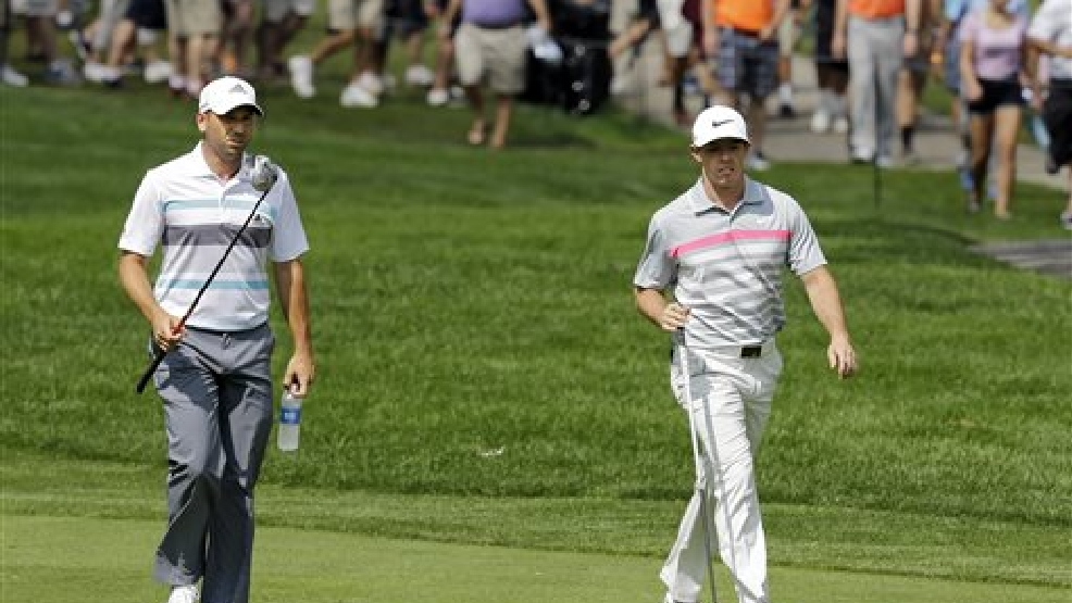 Sergio Garcia, left, and Rory McIlroy walk up the second fairway during the final round of the Bridgestone Invitational golf tournament Sunday, Aug. 3, 2014, at Firestone Country Club in Akron, Ohio. (AP Photo/Mark Duncan)