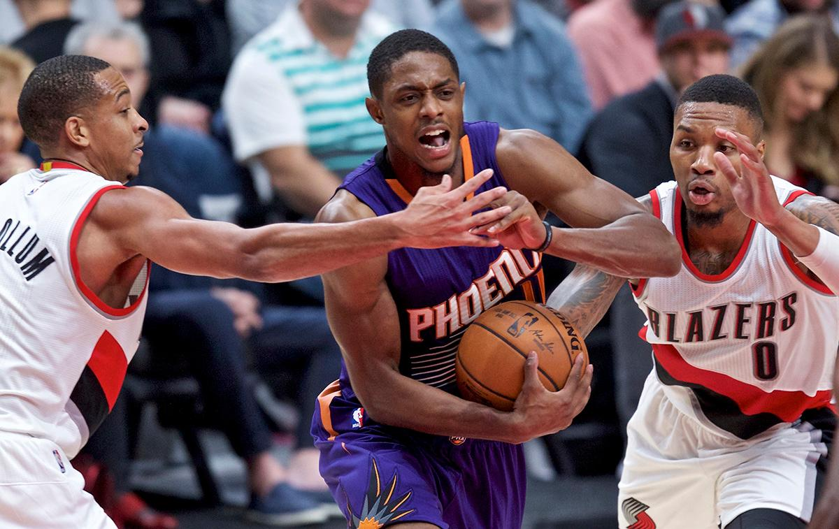 Phoenix Suns guard Brandon Knight, center, drives to the basket between Portland Trail Blazers guards C.J. McCollum, left, and Damian Lillard during the second half of an NBA basketball game in Portland, Ore., Tuesday, Nov. 8, 2016. (AP Photo/Craig Mitchelldyer)