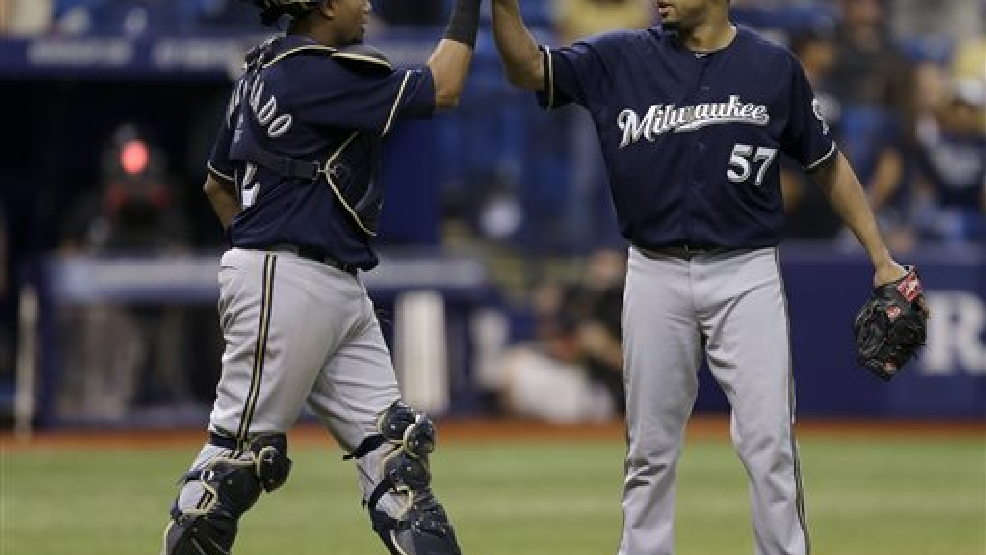 Milwaukee Brewers' Francisco Rodriguez (57) high-fives catcher Martin Maldonado after the team defeated the Tampa Bay Rays 5-0 during an interleague baseball game Wednesday, July 30, 2014, in St. Petersburg, Fla. (AP Photo/Chris O'Meara)