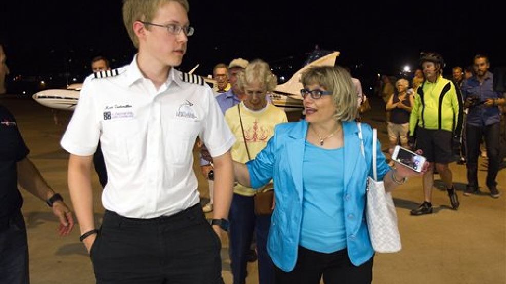 Matt Guthmiller, right, the youngest pilot to fly solo around the world, walks with his mother Shirley after arriving at Gillespie Field in El Cajon, Calif. on Monday, July 14, 2014. The 19-year-old Massachusetts Institute of Technology student from South Dakota, left May 31 from Gillespie Field to circumnavigate the globe in a leased 1981 prop-powered, single-engine Beechcraft Bonanza A36. (AP Photo/U-T San Diego, Sean M. Haffey)