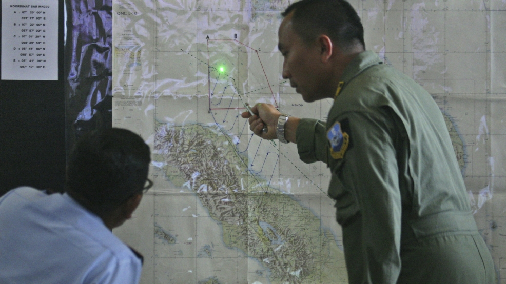 Indonesian Air Force officers examine a map of the Malacca Strait during a briefing following a search operation for the missing Malaysia Airlines Boeing 777, at Suwondo air base in Medan, North Sumatra, Indonesia, Wednesday, March 12, 2014. (AP Photo/Binsar Bakkara)