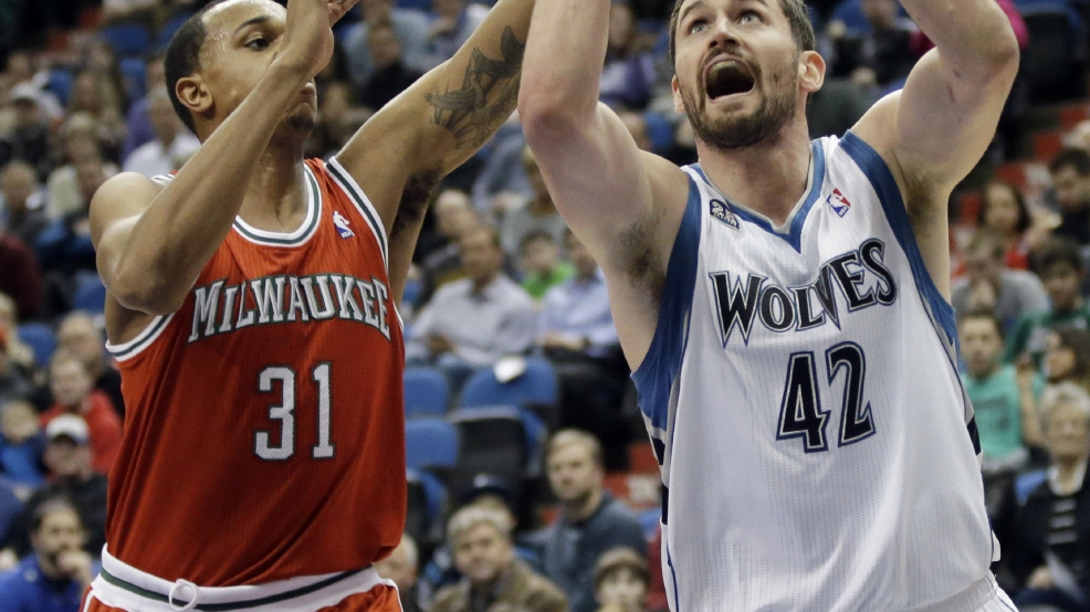 Minnesota Timberwolves' Kevin Love, right, shoots as Milwaukee Bucks' John Henson defends in the first quarter of an NBA basketball game, Tuesday, March 11, 2014, in Minneapolis. (AP Photo/Jim Mone)