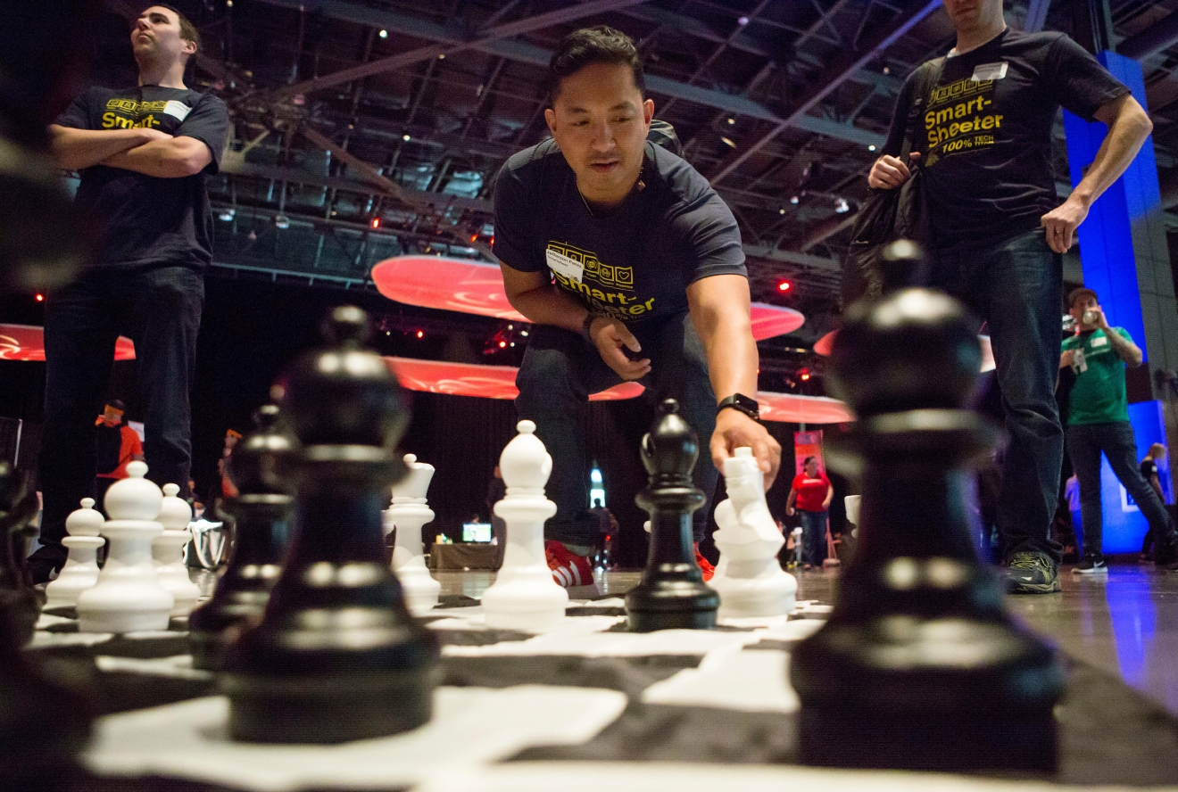 Jefferson Perez carefully makes a move on a massive chessboard at the 6th annual Geekwire Bash at the CenturyLink Event Center. (Sy Bean / Seattle Refined)