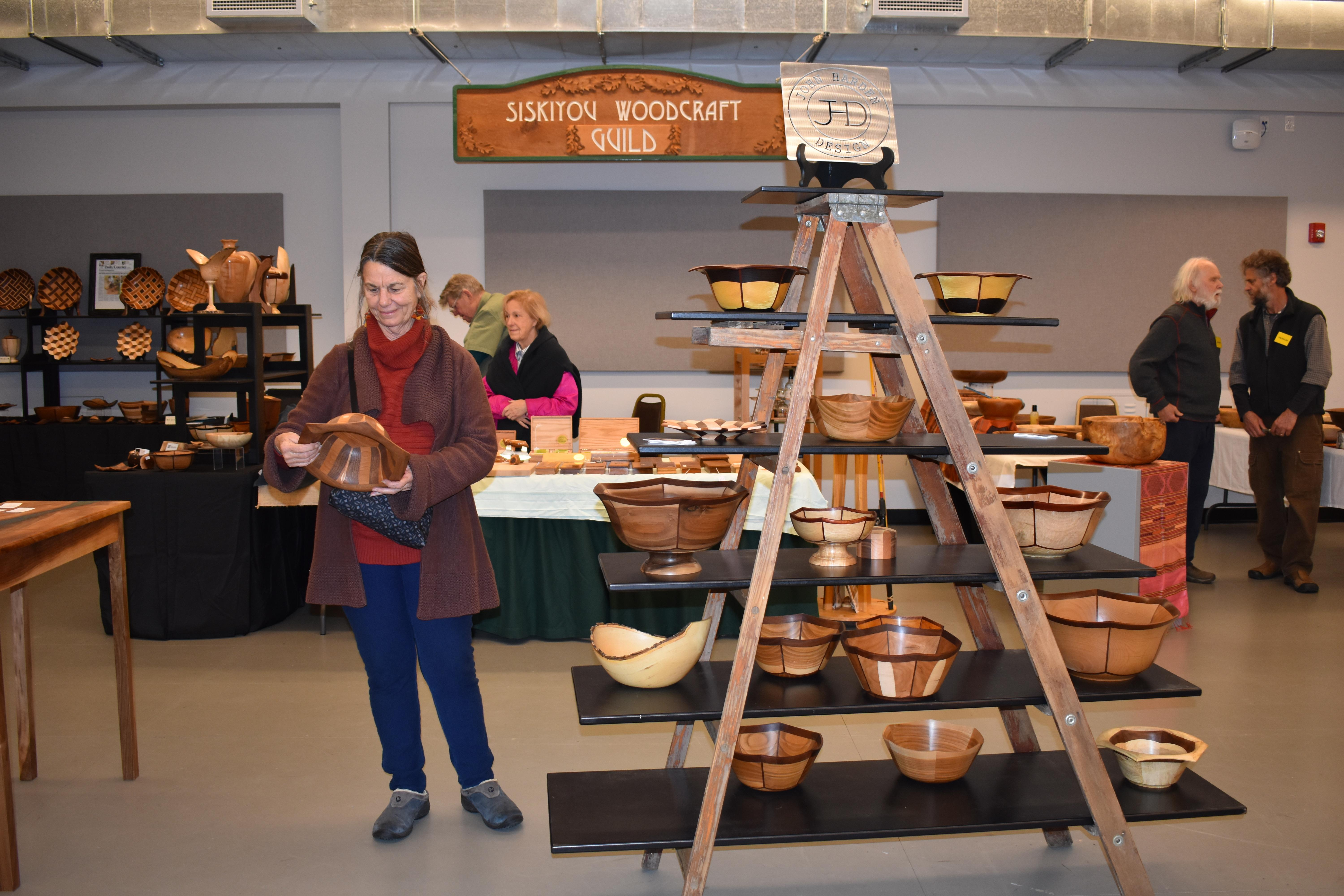 Wendy Seldon of Ashland examines a turned and segmented bowl with inlaid features made by John Harden of Grants Pass. Photo by Maureen Flanagan Battistella