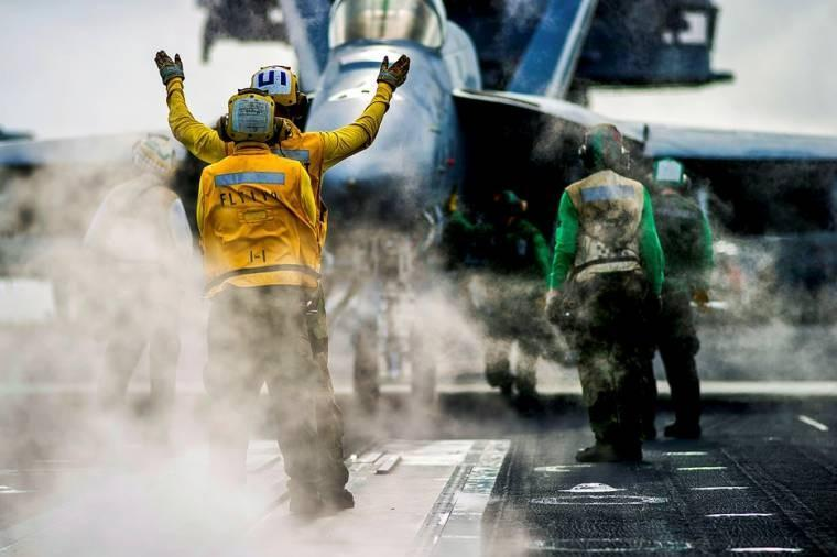 An aircraft handler directs an F/A-18 Super Hornet into position to launch from the flight deck of aircraft carrier USS George Washington in the South China Sea.