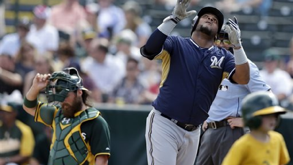 Milwaukee Brewers' Juan Francisco, right, looks skyward after hitting his second home run of the day as Oakland Athletics catcher Derek Norris, left, looks on during the second inning of a spring training baseball game on Thursday, Feb. 27, 2014, in Scottsdale, Ariz. (AP Photo/Gregory Bull)