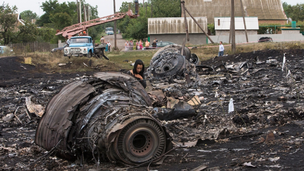 A woman walks at the site of a crashed Malaysia Airlines passenger plane near the village of Rozsypne, eastern Ukraine Friday, July 18, 2014. Rescue workers, policemen and even off-duty coal miners were combing a sprawling area in eastern Ukraine near the Russian border where the Malaysian plane ended up in burning pieces Thursday, killing all 298 aboard. (AP Photo/Dmitry Lovetsky)