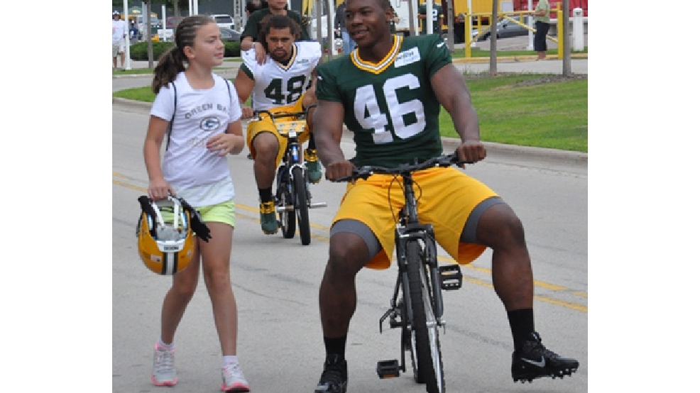 Green Bay Packers linebacker Andy Mulumba chats with a young fan whose bicycle he borrowed to get to training camp practice, July 26, 2013. (WLUK/Angela Kelly)