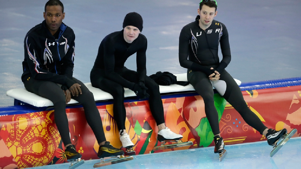 Seated left to right, U.S. speedskaters Shani Davis, Tucker Fredericks and Jonathan Garcia watch others train during the 2014 Winter Olympics in Sochi, Russia, Wednesday, Feb. 5, 2014. (AP Photo/Matt Dunham)