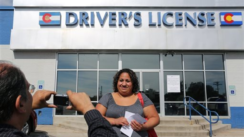 Immigrant and longtime resident in the United States Rosalva Mireles is photographed by Jesus Sanchez of Spanish language newspaper El Commercio, after Mireles was processed for her permanent driver's license, and received a temporary license, at a Department of Motor Vehicles office, in Denver, Friday Aug. 1, 2014. Colorado began issuing driver's licenses and identification cards on Aug. 1, 2014 to immigrants who are in the country, regardless of legal immigration status. (AP Photo/Brennan Linsley)