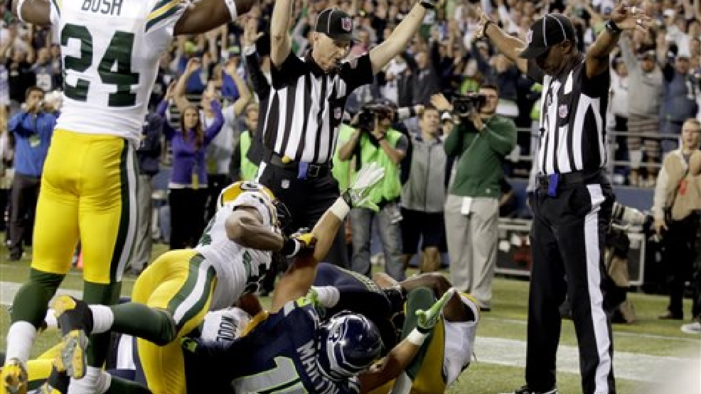 "FILE - In this Sept. 24, 2012, file photo, an official, rear center, signals for a touchdown by Seattle Seahawks wide receiver Golden Tate, obscured, as another official, at right, signals a touchback, on the controversial last play of an NFL football game against the Green Bay Packers in Seattle. It's been nearly two full years since the Packers and Seahawks met in the regular season, a game that forever became known as the ""Fail Mary,"" for the disputed touchdown on the final play. Both teams say that result has no relevance to Thursday night's, Sept. 4, 2014, season opener, even if no one will ever forget the play. (AP Photo/Stephen Brashear, File)"