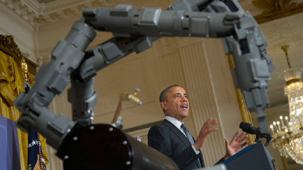 President Barack Obama, stands next to a robotic arm, as he speaks about manufacturing innovation institutes, Tuesday, Feb. 25, 2014, in the East Room of the White House in Washington. Obama announced new Pentagon and private-sector partnerships aimed at beefing up advanced manufacturing technology in the US to be based initially in Chicago and Detroit. The partnerships are funded with $140 million from the Pentagon and matched by area university and business consortiums. (AP Photo/Pablo Martinez Monsivais)