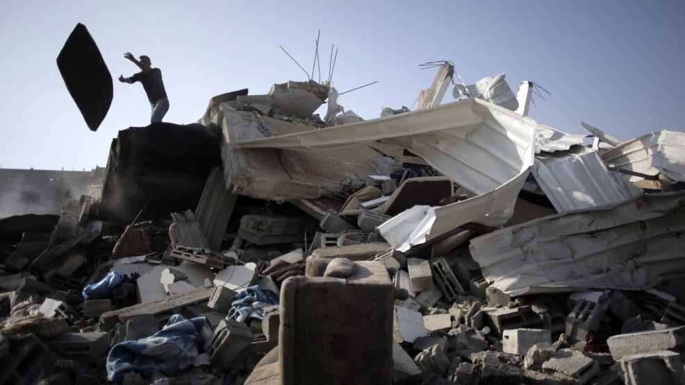 A Palestinian sifts through rubble from the damage of their house after it was destroyed in an Israeli strike late Friday, in Gaza City, Saturday, Aug. 23, 2014. (AP Photo/Khalil Hamra)