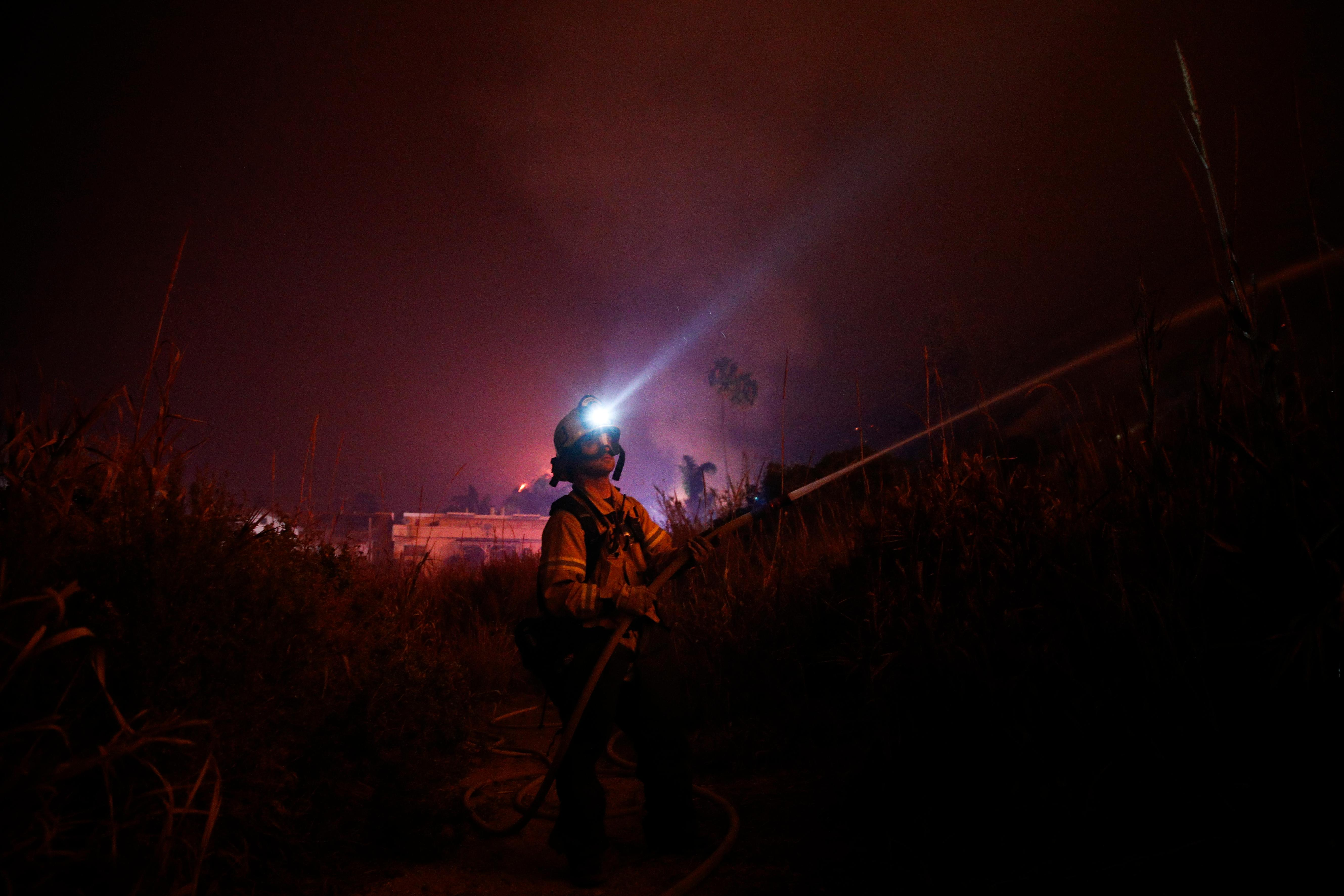 Firefighter Ryan Spencer battles a wildfire as it burns along a hillside toward homes in La Conchita, Calif., Thursday, Dec. 7, 2017. The wind-swept blazes have forced tens of thousands of evacuations and destroyed dozens of homes. (AP Photo/Jae C. Hong)