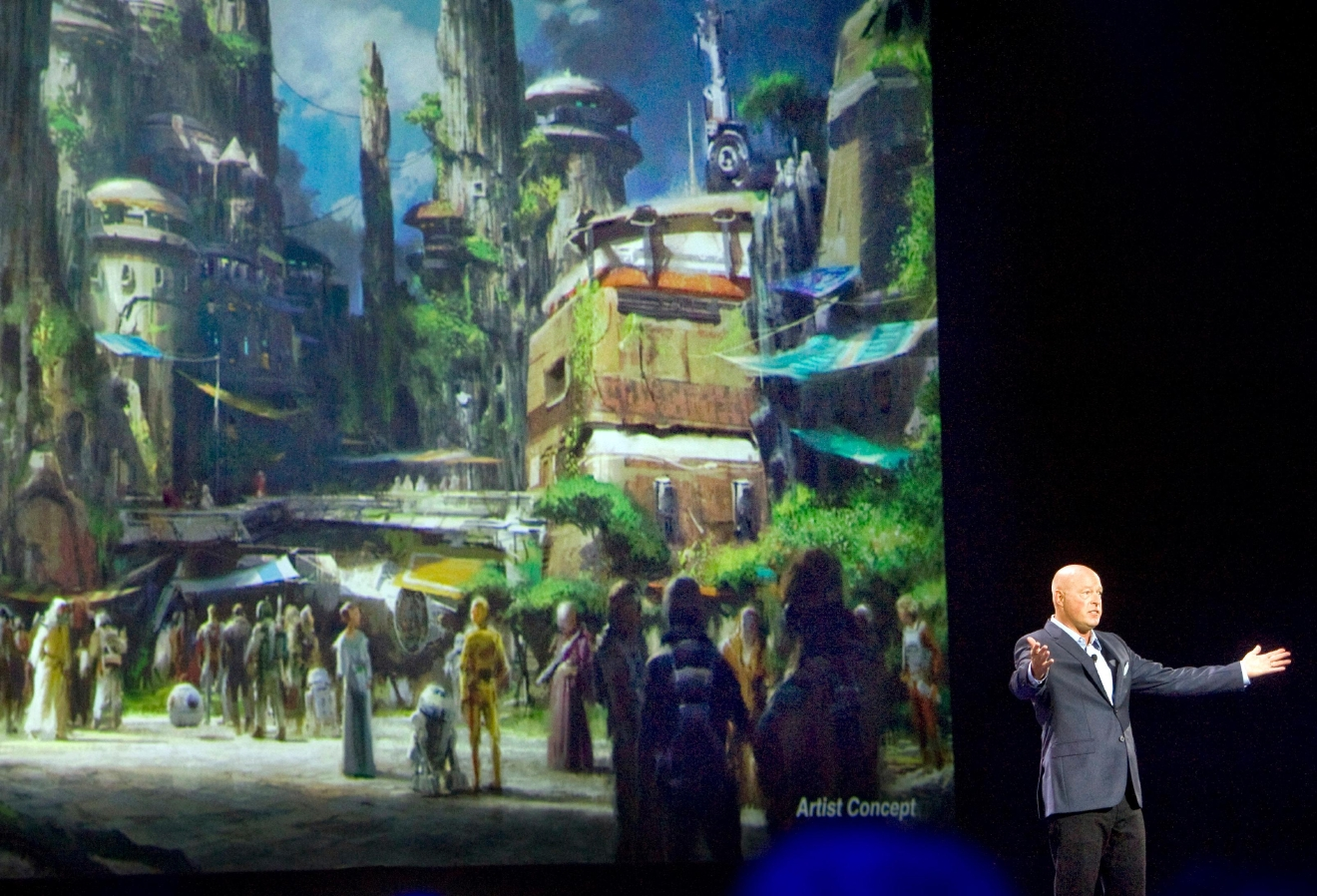 FILE - In this Saturday, Aug. 15, 2015, file photo, Bob Chapek, chairman of Walt Disney Parks and Resorts, speaks in front of concept art of the newly announced Star Wars Land at the D23 Expo in Anaheim, Calif. Disney CEO Bob Iger said Tuesday, Feb. 7, 2017, the company will open its Star Wars-themed lands at California's Disneyland and Florida's Walt Disney World in 2019. (Mindy Schauer/The Orange County Register via AP, File)