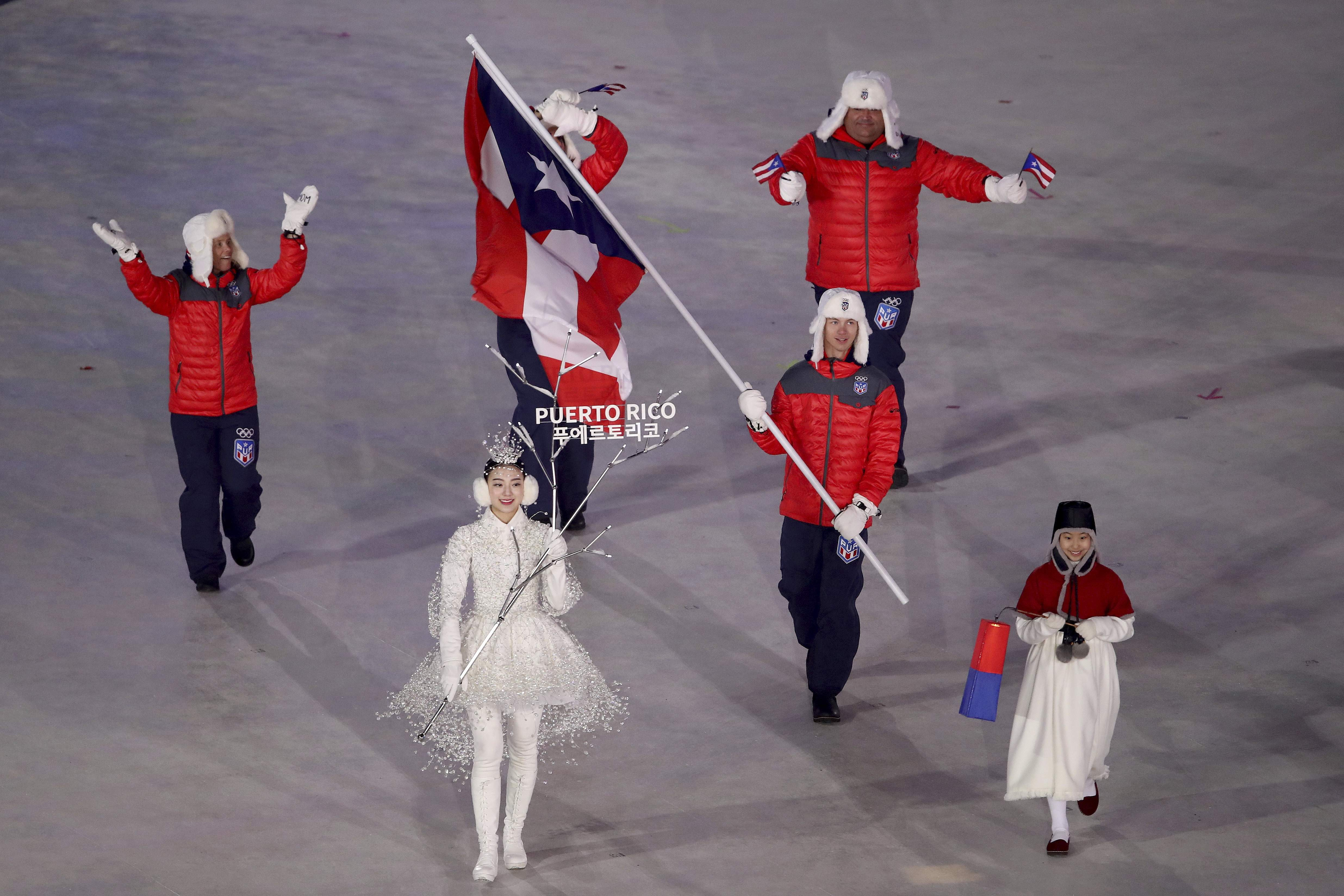 Charles Flaherty carries the flag of Puerto Rico during the opening ceremony of the 2018 Winter Olympics in Pyeongchang, South Korea, Friday, Feb. 9, 2018. (Sean Haffey/Pool Photo via AP)