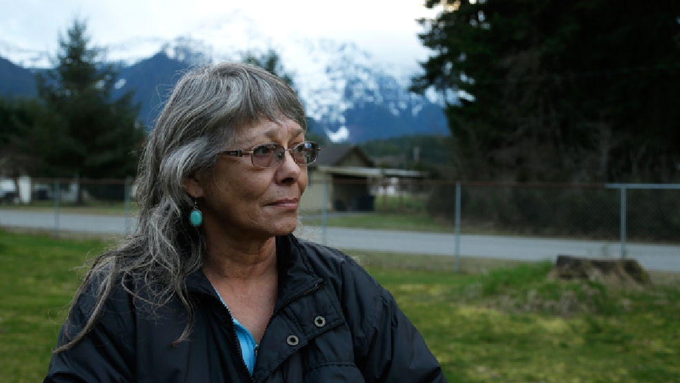 Robin Youngblood poses for a photo Thursday, March 27, 2014, with Whitehorse Mountain behind her in Darrington, Wash. Youngblood survived the massive mudslide that hit the nearby community of Oso, Wash. last Saturday, and was rescued by a helicopter as she floated on a piece of a roof. (AP Photo/Ted S. Warren)