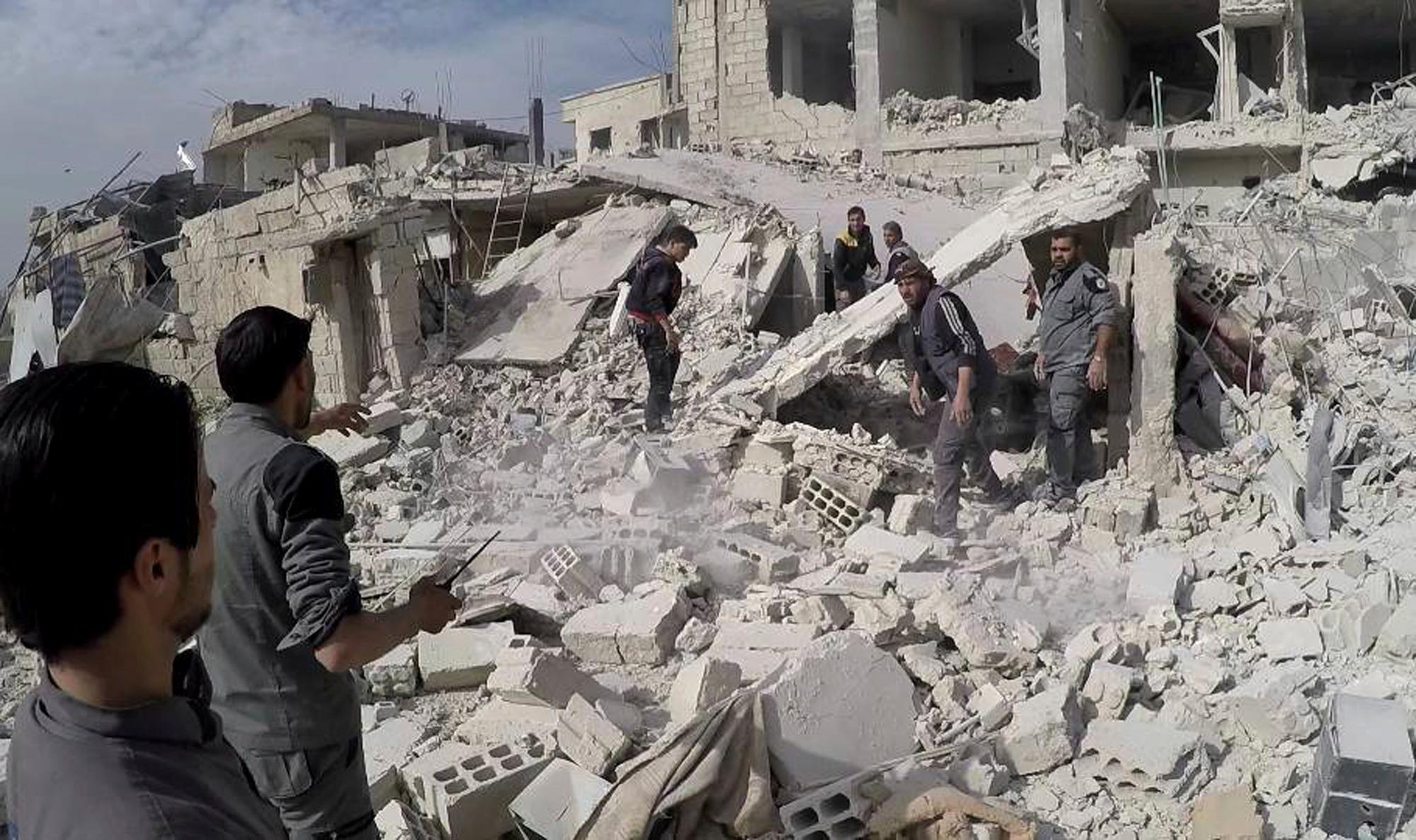 This photo provided by the Syrian Civil Defense White Helmets, which has been authenticated based on its contents and other AP reporting, shows civil defense workers and civilians inspecting a damaged building after airstrikes hit a rebel-held suburb near Damascus, Syria, Thursday, Feb. 8, 2018. Syrian rescue workers and activists say the death toll from ongoing government strikes on the opposition-held region near the capital Damascus has risen to at least 35. (Syrian Civil Defense White Helmets via AP)