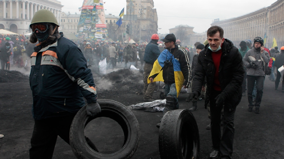 Activists carry car tires in Kiev's Independence Square, the epicenter of the country's current unrest, Thursday, Feb. 20, 2014. Fierce clashes between police and protesters, some including gunfire, shattered a brief truce in Ukraine's besieged capital Thursday, killing numerous people. The deaths came in a new eruption of violence just hours after the country's embattled president and the opposition leaders demanding his resignation called for a truce and negotiations to try to resolve Ukraine's political crisis. (AP Photo/Sergei Chuzavkov)
