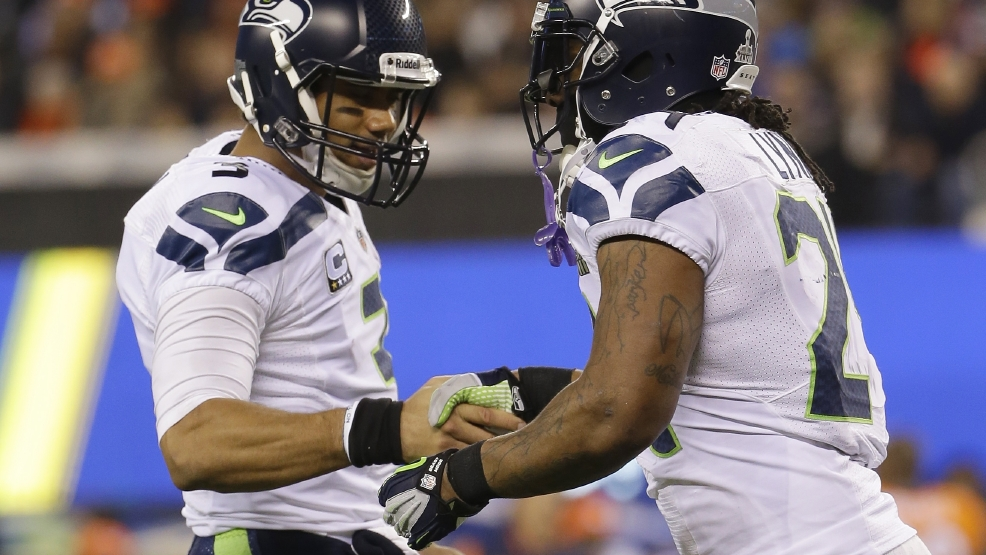 Seattle Seahawks' Russell Wilson, left, celebrates with teammate Marshawn Lynch during the first half of the NFL Super Bowl XLVIII football game against the Denver Broncos Sunday, Feb. 2, 2014, in East Rutherford, N.J. (AP Photo/Matt Slocum)