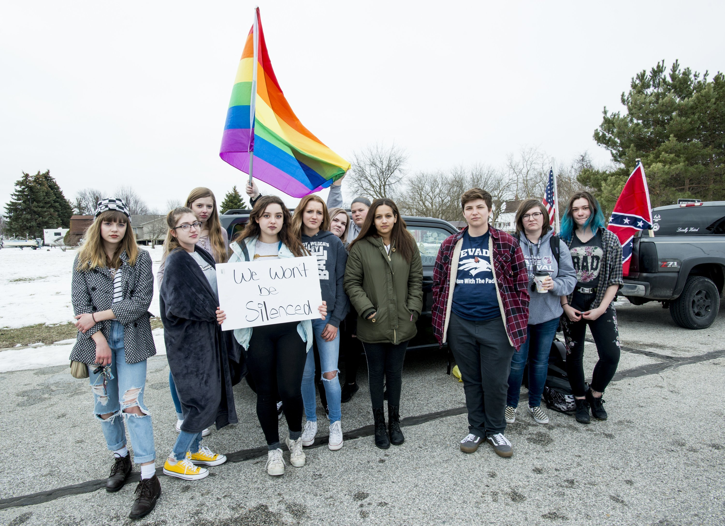 "Counter-protesters display rainbow flags and signs as a caravan of Confederate-flag-bearing trucks park along the outer drive of Bay City Western High School in Auburn, Mich., Wednesday, April 18, 2018. ""We have such a small minority population of students and we're in a conservative area"" said Kendrix Szilagyi, pictured at center left with a sign. ""If they went to Saginaw or Bay City Central they wouldn't let this happen""(Jacob Hamilton/The Bay City Times via AP)"