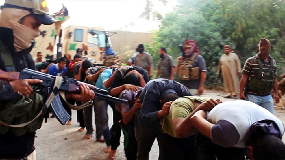 "This file image posted on a militant website on Saturday, June 14, 2014, which has been verified and is consistent with other AP reporting, appears to show militants from the Islamic State group leading away captured Iraqi soldiers dressed in plain clothes after taking over a base in Tikrit, Iraq. Human Rights Watch, a leading international watchdog, said Wednesday, Sept 3, 2014, new evidence indicates the Islamic State fighters killed between 560 and 770 men captured at Camp Speicher, near the city of Tikrit — a figure several times higher than what was initially reported. The Human Rights Watch statement said the revised figure for the slain soldiers was based on analysis of new satellite imagery, militant videos and a survivor's account that confirmed the existence of three more ""mass execution sites."" (AP Photo via militant website, File)"