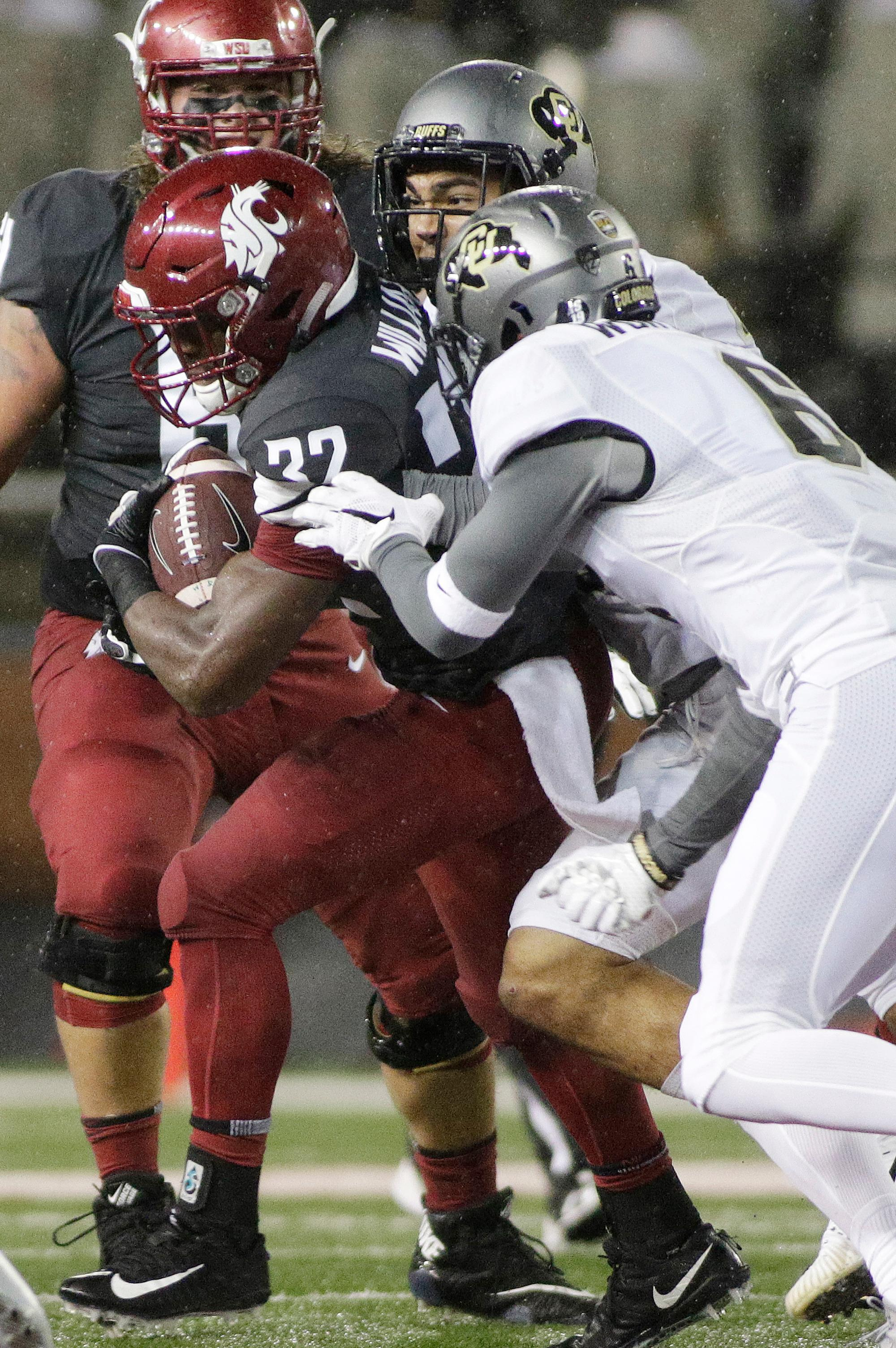 Colorado defensive back Evan Worthington, right, and linebacker Drew Lewis, center, tackle Washington State running back James Williams during the first half of an NCAA college football game in Pullman, Wash., Saturday, Oct. 21, 2017. (AP Photo/Young Kwak)