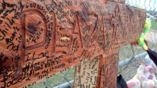 Well wishes have been written on a cross for Plaza Towers Elementary victims.