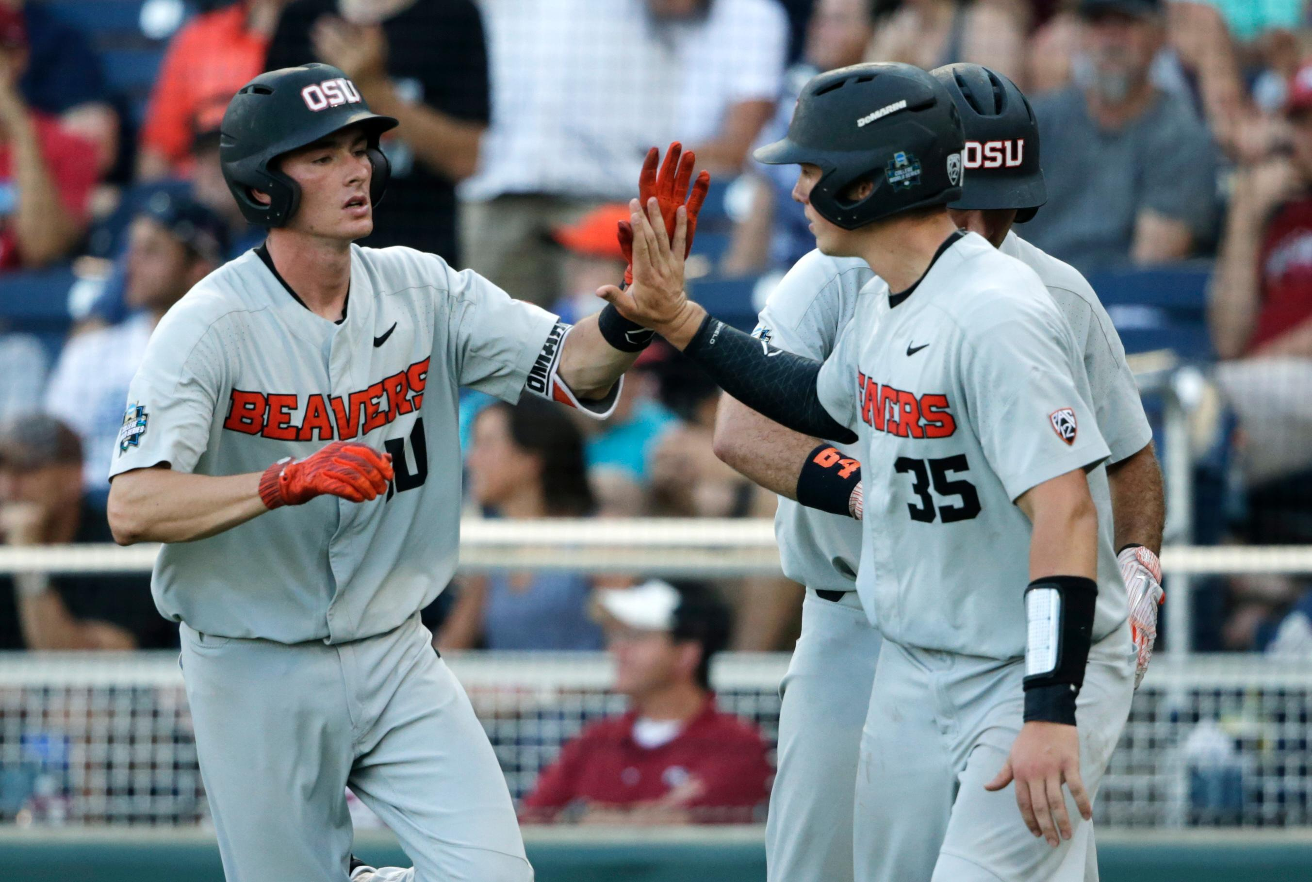 Oregon State third baseman Michael Gretler, left, greets Adley Rutschman (35) after Rutschman scored on a sacrifice fly hit by Gretler during the fifth inning against Arkansas in Game 3 of the NCAA College World Series baseball finals, Thursday, June 28, 2018, in Omaha, Neb. (AP Photo/Nati Harnik)