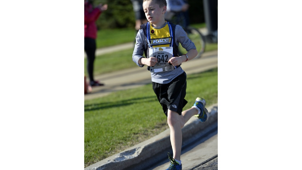 In this photo taken May 3, 2014, Noah Bliss runs the Wisconsin Marathon and Half Marathon along Kenosha's lakefront in Kenosha, Wis. Bliss, 10, started long-distance running just over two years ago. His run in an event earlier this month is the fastest on record for his age group, according to the Association of Road Racing Statisticians, which tracks races worldwide. Guinness World Records doesn't track age-specific race results. Bliss ran 13.1 miles in 1 hour, 37 minutes and 15 seconds, the fastest in the world among 10-year-old boys, according to ARRS. (AP Photo/Kenosha News, Brian Passino)