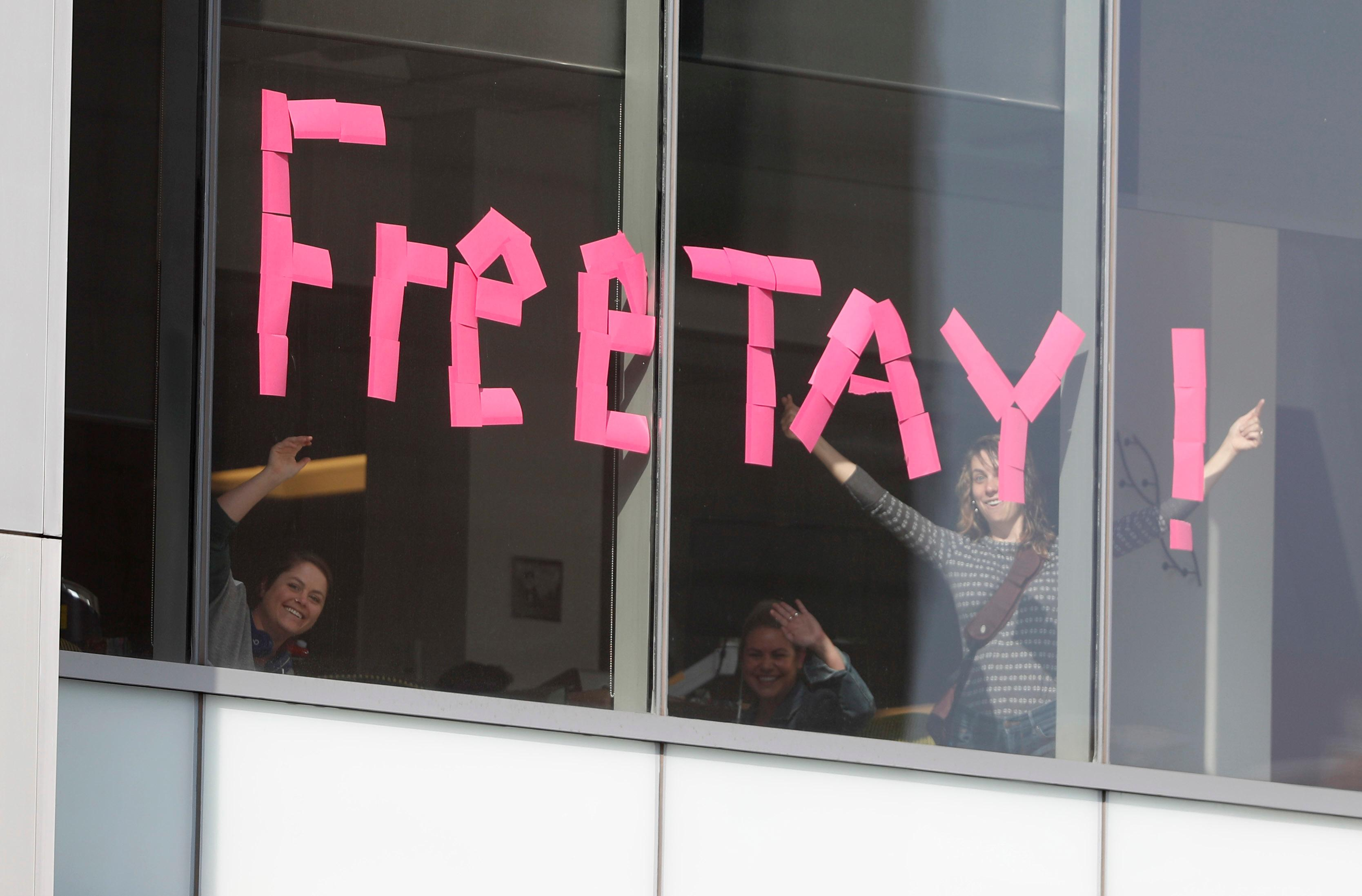 Workers put up sign in support of pop singer Taylor Swift in an office building across the street from the federal courthouse in Denver on Tuesday, Aug. 8, 2017, during the jury selection phase in a civil trial to determine whether a radio host groped Swift. (AP Photo/David Zalubowski)
