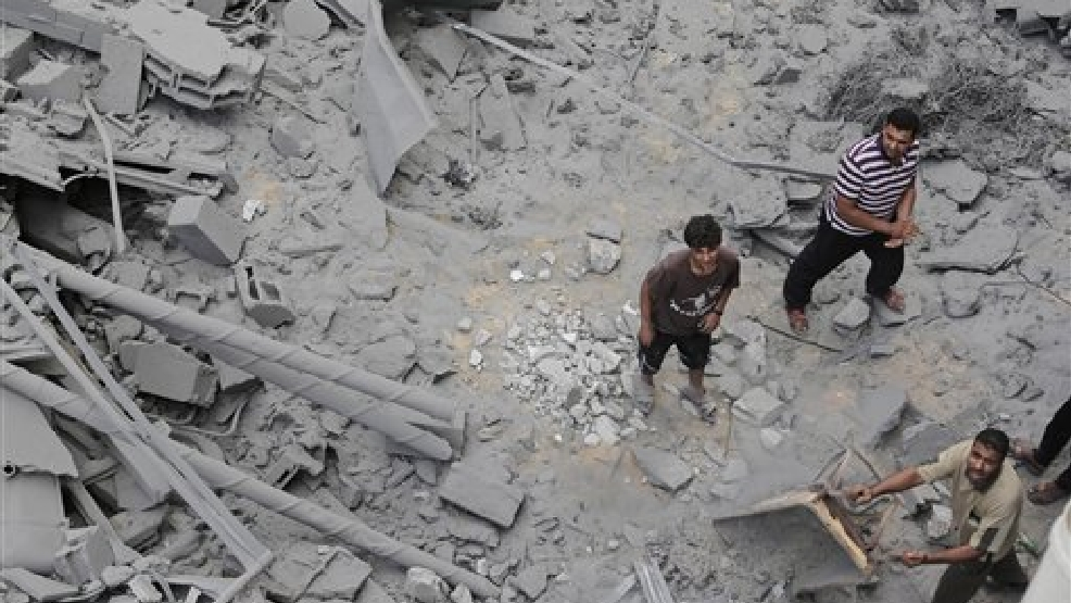 Palestinians from a neighboring apartment building carry out debris as they walk on the rubble of the offices of the Hamas movement's Al-Aqsa satellite TV station, in Gaza City, northern Gaza Strip, destroyed by an Israeli strike, Tuesday, July 29, 2014. Early Tuesday, Israel warplanes struck a series of targets in Gaza City, including the top Hamas leader in Gaza, Ismail Haniyeh's house and government offices, while Gaza's border area with Israel was hit by heavy tank shelling. (AP Photo/Lefteris Pitarakis)