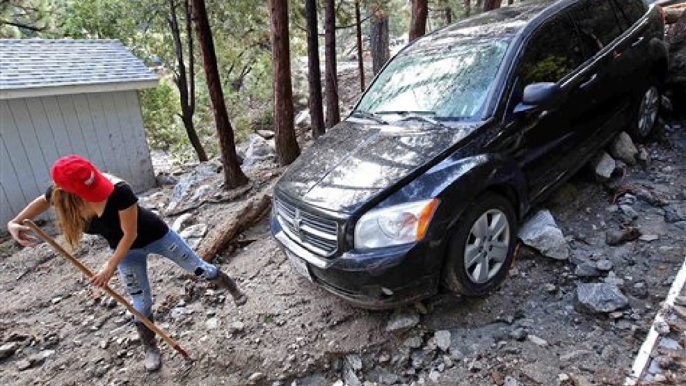 Jessica Gosney digs out her car after rocks and mud inundated her home in the mountain community of Forest Falls in the San Bernardino Mountains Monday, Aug. 4, 2014. Crews cleared roads in an area where some 2,500 had been stranded after thunderstorms caused mountain mudslides in Southern California over the weekend, while authorities estimated that between 6 and 8 homes were badly damaged and likely uninhabitable. One person was found dead in a vehicle that was caught in a flash flood. A group of campers spent the night at a community center near Forest Falls headed. (AP Photo/Nick Ut)