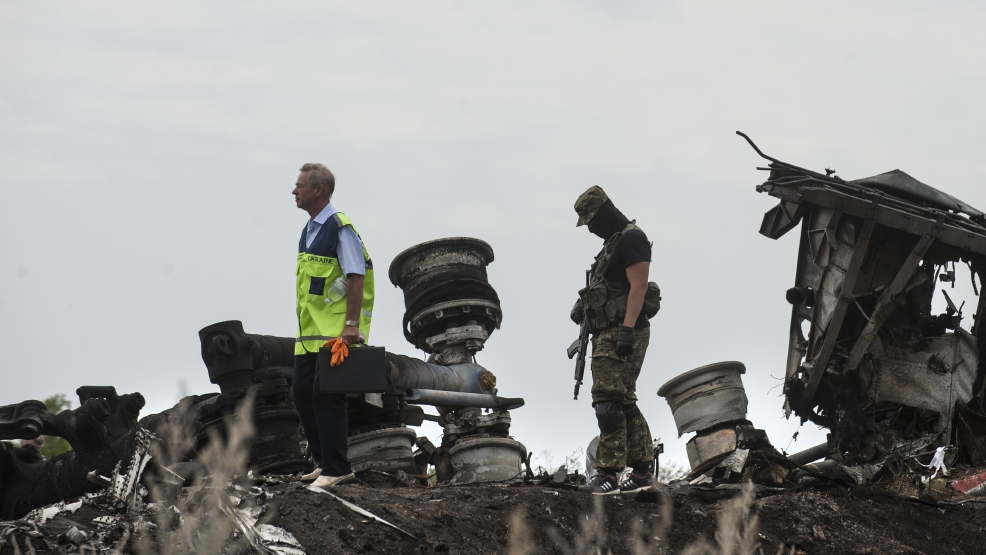 A Ukrainian investigator, left,walks by charred debris as a pro-Russian fighter guards him, at the crash site of Malaysia Airlines Flight 17 near the village of Hrabove, eastern Ukraine, Sunday, July 20, 2014. Rebels in eastern Ukraine took control Sunday of the bodies recovered from downed Malaysia Airlines Flight 17, and the U.S. and European leaders demanded that Russian President Vladimir Putin make sure rebels give international investigators full access to the crash site.(AP Photo/Evgeniy Maloletka)