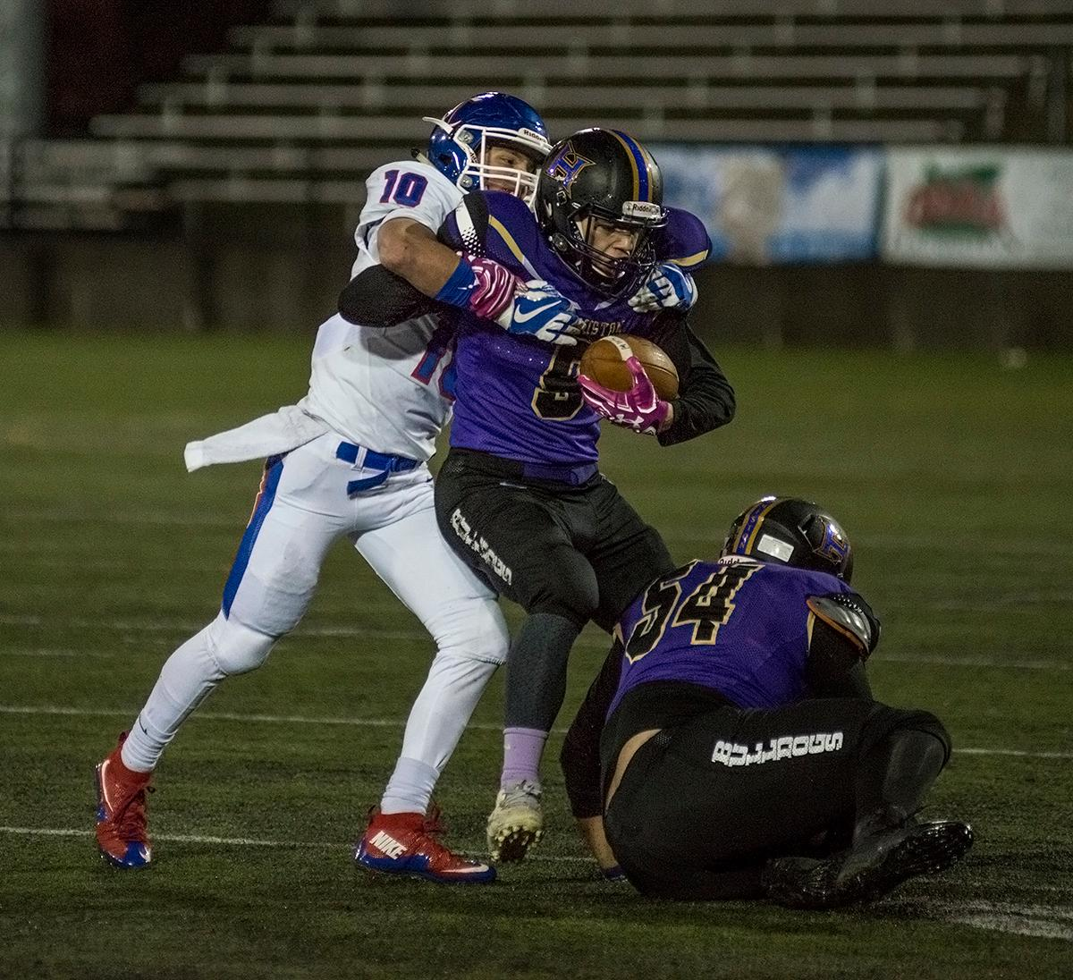 Churchill Lancers defensive back Tyson Bennion (#10) tackles the Hermiston Bulldogs ball carrier to end a play. The Hermiston Bulldogs defeated the Churchill Lancers 38-35 for the 5A state title Saturday evening at Hillsboro Stadium. Photo by Abigail Winn, Oregon News Lab