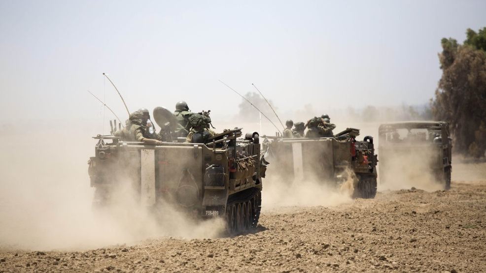 Israeli armored personnel carriers move along the Israel and Gaza border, Saturday, July 19, 2014. Israel pounded Hamas rocket launchers, uncovered more than a dozen cross-border tunnels and engaged in gunbattles with Palestinian militants Saturday, as fighting intensified on the second day of its open-ended ground operation in Gaza, as the Palestinian death toll continued to rise. (AP Photo/Dusan Vranic)