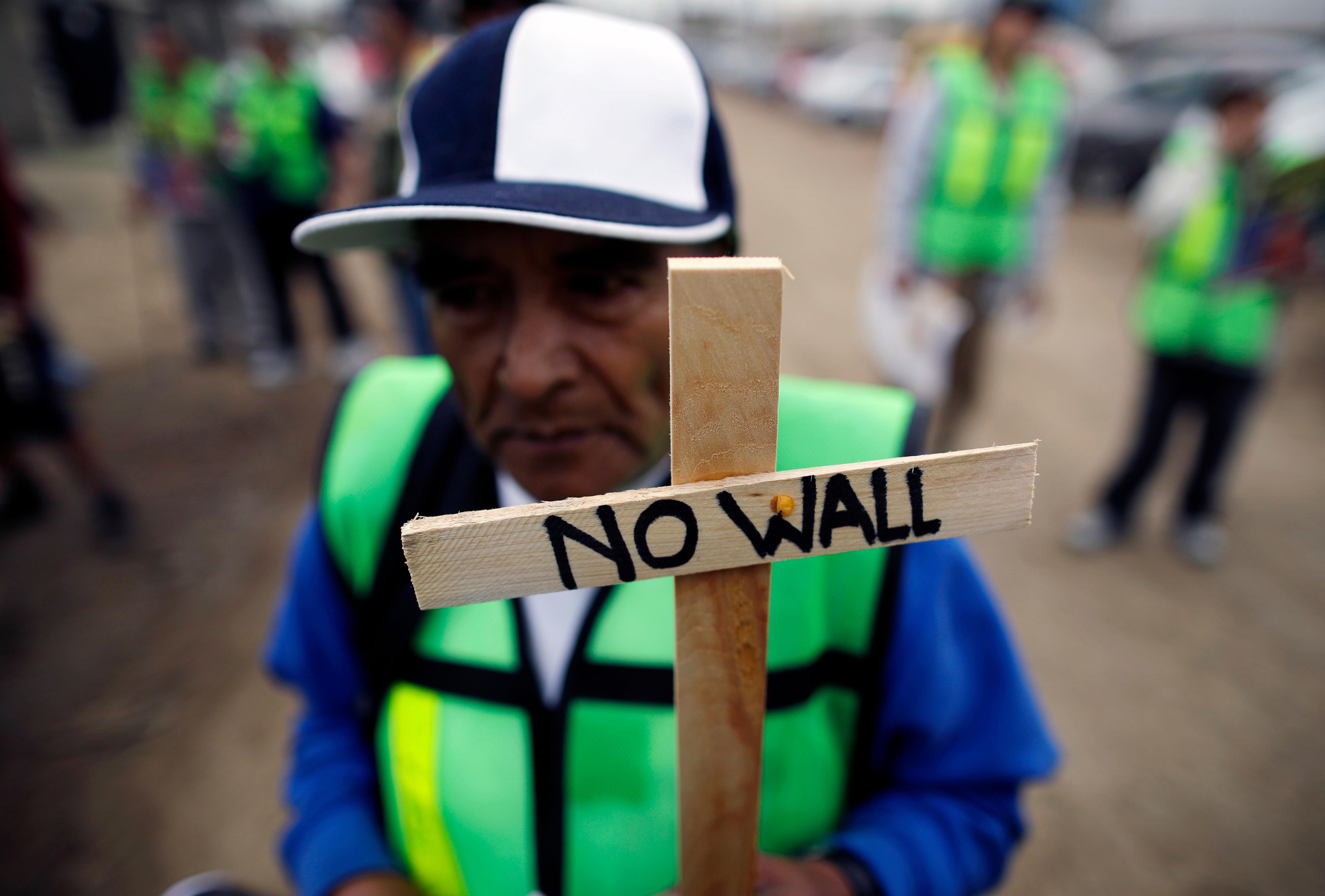 Roberto Perez Garcia of Mexico participates in a rally against the border wall on Tuesday, March 13, 2018, in Tijuana, Mexico. President Trump is scheduled to visit the site of the border wall prototypes in the United States, which can be seen from where the protesters are gathering on the Mexico side. (AP Photo/Gregory Bull)