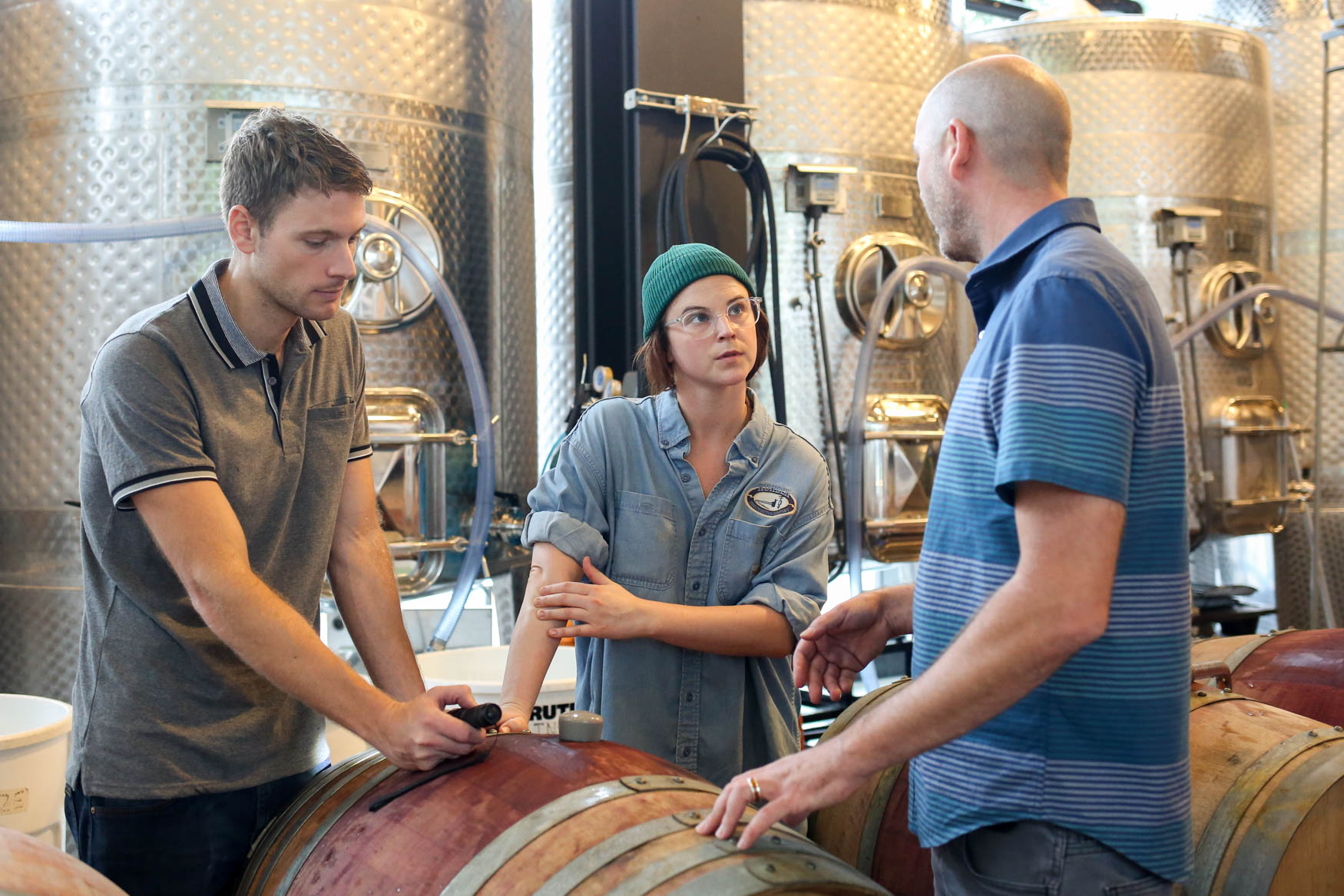 Conor McCormack, right, talks to cellar worker Claire Corbin and winery production manager Erik Subrizi.{ } (Amanda Andrade-Rhoades/DC Refined)