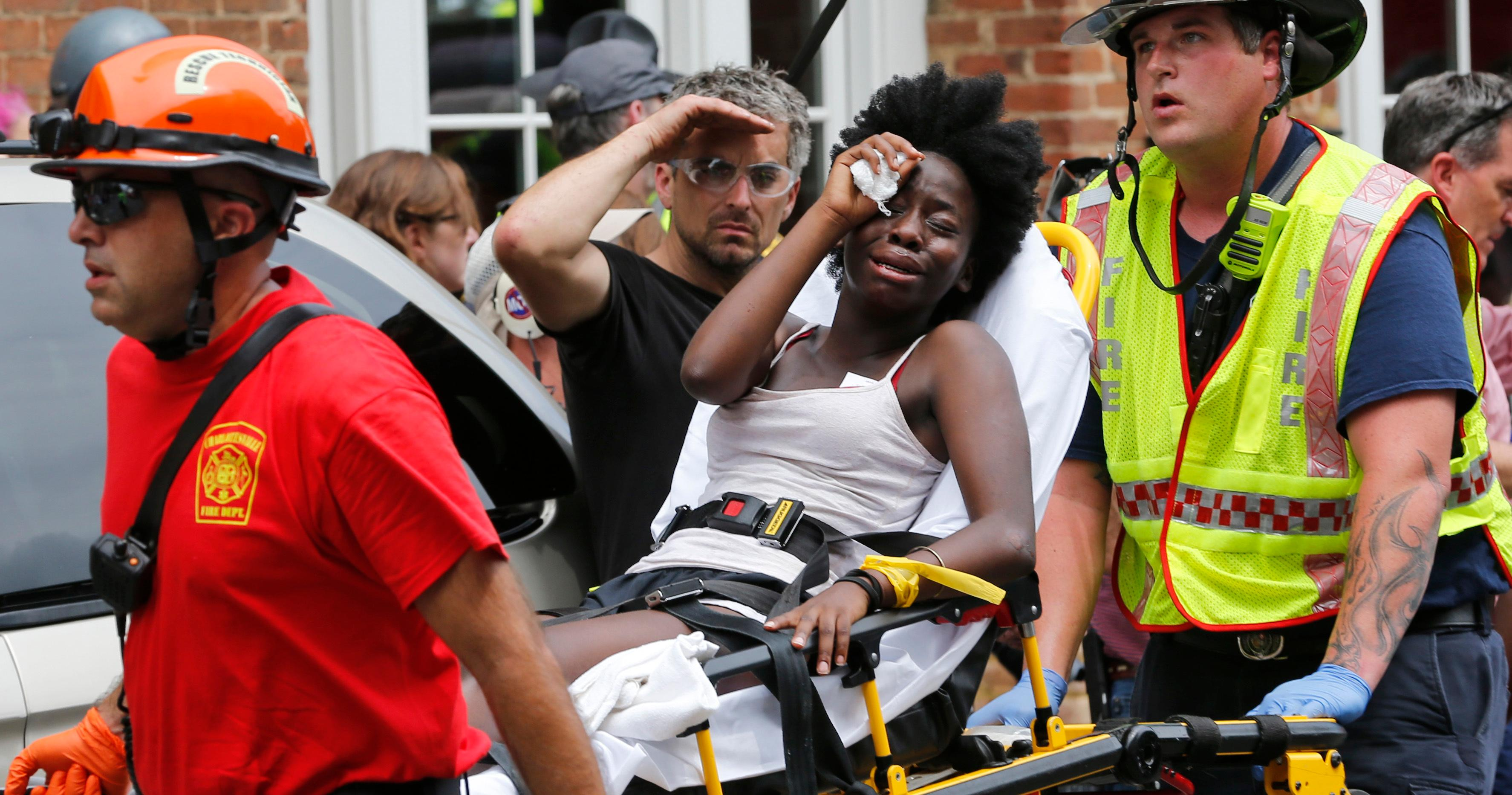 Rescue personnel help an injured woman after a car ran into a large group of protesters after an white nationalist rally in Charlottesville, Va., Saturday, Aug. 12, 2017.  The nationalists were holding the rally to protest plans by the city of Charlottesville to remove a statue of Confederate Gen. Robert E. Lee. There were several hundred protesters marching in a long line when the car drove into a group of them.(AP Photo/Steve Helber)