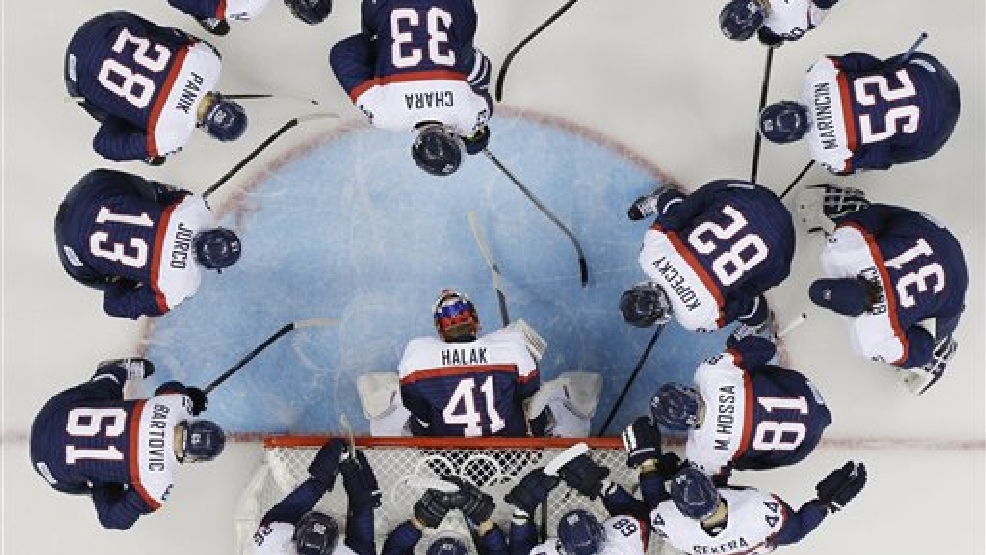 Team USA huddles around the net before their game against Slovakia during the 2014 Winter Olympics men's ice hockey game at Shayba Arena, Thursday, Feb. 13, 2014, in Sochi, Russia. (AP Photo/Matt Slocum)
